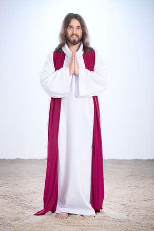 Jesus Christ standing on sand and smiling Stock Photo