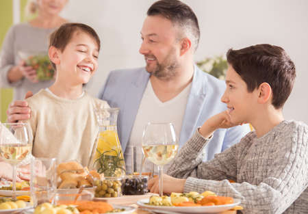 Happy father talking to his sons and smiling Stock Photo
