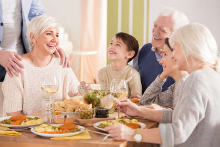 Parents sharing memories with family at the dinner Stock Photo