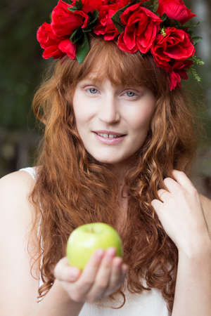Young ginger woman with red flowers in her hair holding green apple