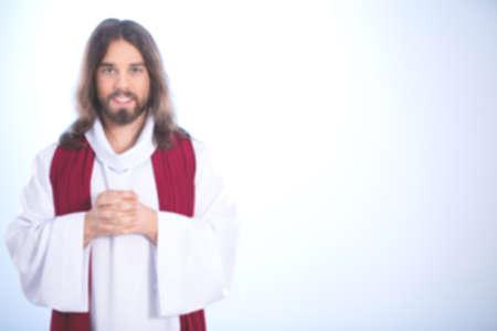 Blurry Jesus Christ smiling on light background