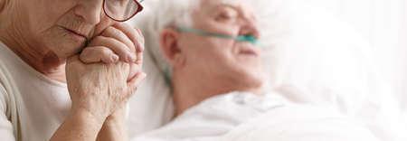 Doodende patiënt op een ziekenhuisbed en zijn vrouw die zijn hand vasthoudt Stockfoto