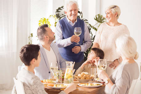 Happy grandpa making a speech at a celebration dinner Stock Photo