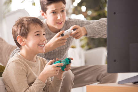 Two boys playing a video game at family dinner