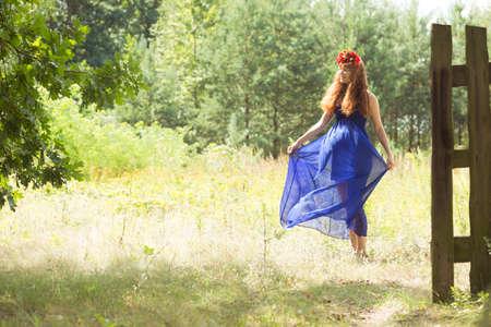 стиль жизни: Имбирь природная красота с цветком венок и длинные синие платья, танцующие в лесу
