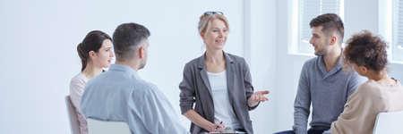 Jonge patiënten rond lachende ondersteunende therapeut in groepstherapie sessie