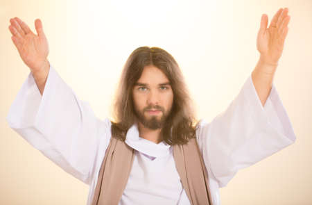 Christ standing with hands up on light background Stock Photo