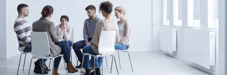 People sitting in a circle with psychologist in group therapy Stock Photo
