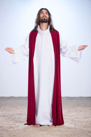 Jesus Christ standing barefoot on the sand
