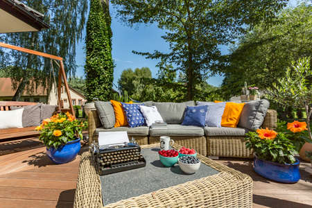 typewriting: Big terrace with garden furniture and typewriter and fruits on a table