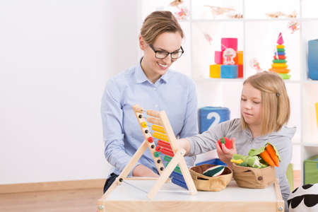 Female tutor and little girl counting with abacus in playroom Banque d'images