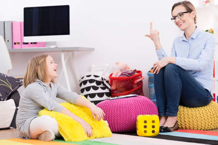Psychotherapist woman using play activities for teaching young girl to count Imagens