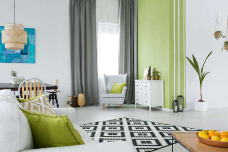 ソファ、椅子、ドレッサー、テーブルと緑と白のインテリア