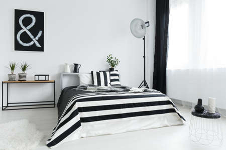 Double bed and stylish, black and white decorations in modern bedroom