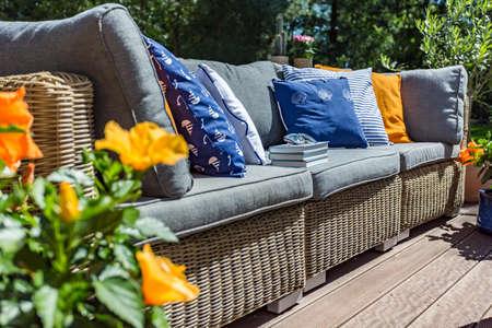 많은 베개, 책 및 화분에 담긴 꽃이있는 정원용 소파