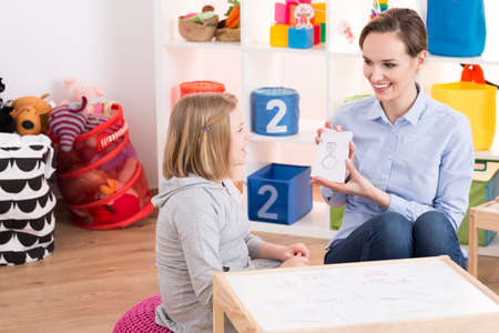 Child counselor showing drawings to little smart girl with ADHD