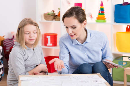 Young female therapist and little girl during play therapy session Stock Photo