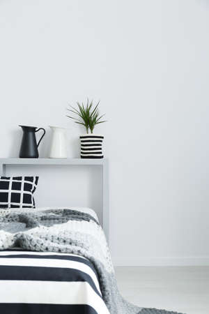 Bed with soft, grey blanket and black and white decorations Stock Photo