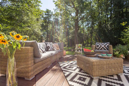 surrounded: Cozy terrace with rattan furniture surrounded by trees