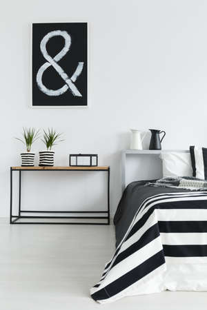 Modern bedroom with wooden table and black and white decorations