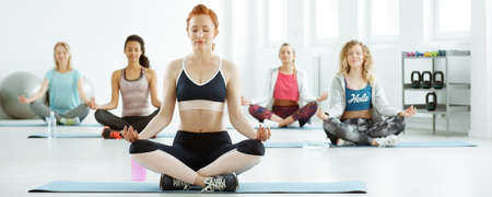 Calm women meditating during fitness classes in the gym