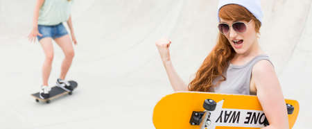Confident teenager in beanie with skateboard making a success gesture