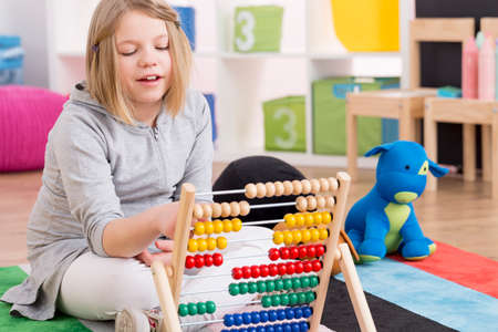 Smart little genius girl playing with abacus in colorful room