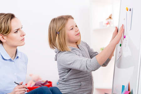 Psychologist using play therapy for testing child with autism disorder Фото со стока
