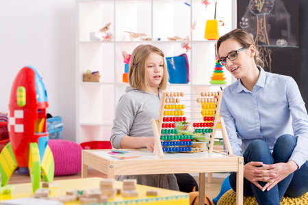Little girl learning to count with her teacher in colorful playroom Stock Photo
