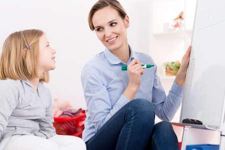 ADHD를 가진 어린 소녀와 일하고 치료 문제를 읽는 치료사