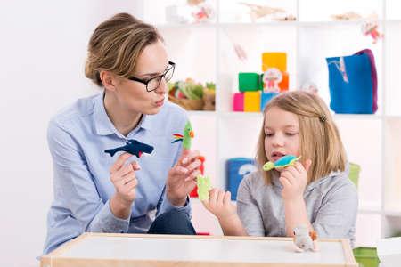 아이와 함께 놀이 치료 중 화려한 장난감을 사용하여 여성 교사