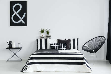 Black and white bedroom with modern chair and night table Foto de archivo