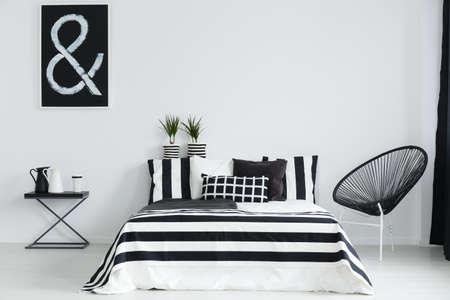 Zwart-witte slaapkamer met moderne stoel en nachtkastje Stockfoto