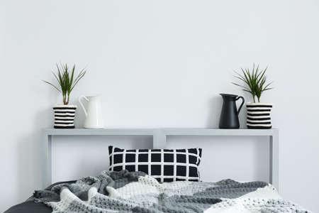 ダブルベッド、灰色の毛布、チェック クッション、装飾的な植物
