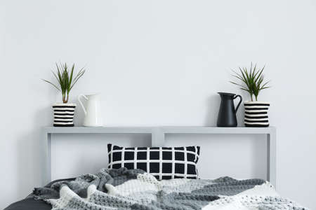 Double bed, grey blanket, checked cushion and decorative plants Stok Fotoğraf
