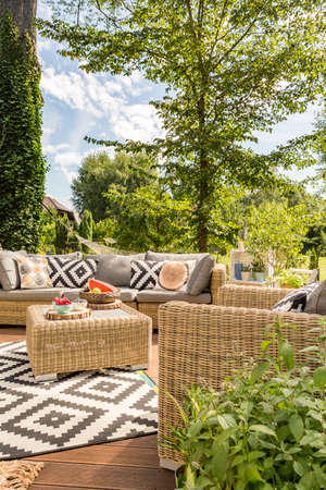 Outdoor terrace with rattan furnitures and accessories in scandi style