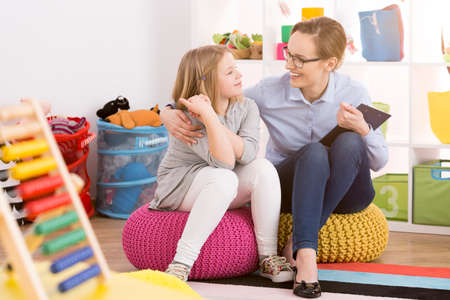 Young speech therapist working with child in colorful educational playroom Stock Photo