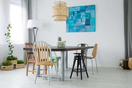 Witte eetkamer met planten, houten tafel, stoelen en lamp