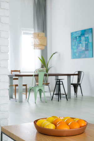 White dining room with communal table, chairs and trendy lamp
