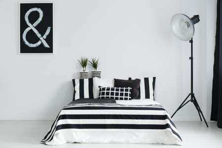 Black and white bedroom with double bed and floor lamp