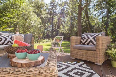 정원에서 무늬 베개가있는 아름다운 목조 테라스