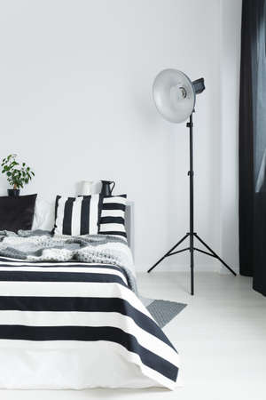 Bed with striped, black and white bedding and floor lamp