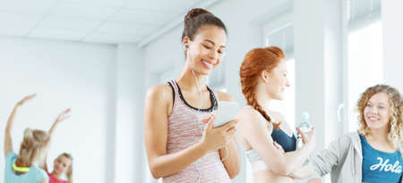 earbud: Young woman smiling and listening to music at the gym