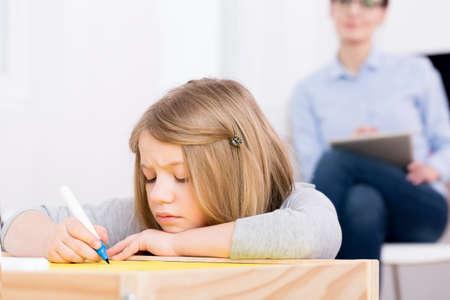 mujer pensativa: Terapeuta observando aburrida niña triste con ansiedad y depresión infantil Foto de archivo