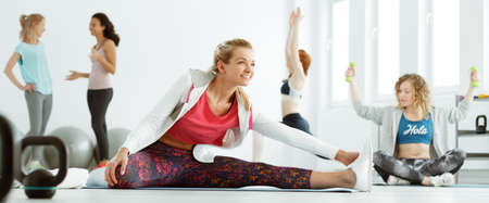 Woman warming up on exercise mat at the gym Stock Photo