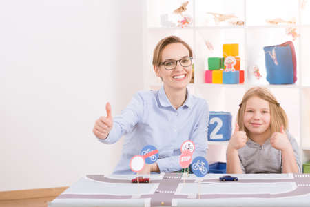 Smart little genius learning traffic regulations with young female teacher