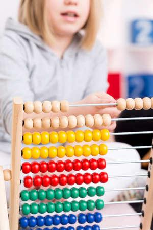 다채로운 줄을 사용하여 계산하는 학습 금발 소녀
