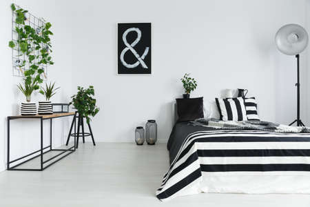 Elegant, black and white bedroom with house plants Stock Photo