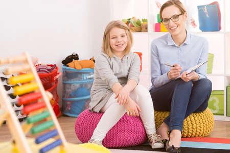 여자 어린이 심리학자와 poufs에 앉아있는 어린 소녀 스톡 콘텐츠