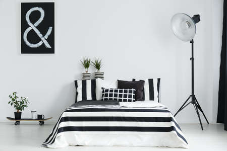 Skateboard, house plants, and floor lamp in modern, stylish bedroom Stock Photo